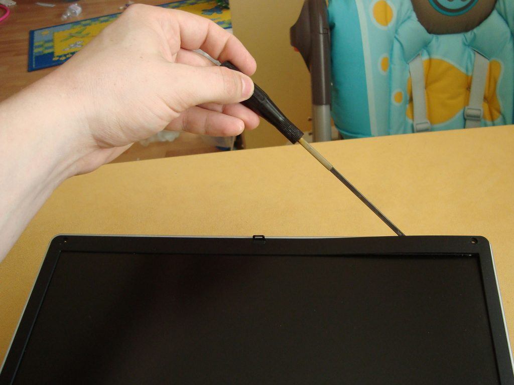 Use screwdriver or guitar pick to release latches around the frame